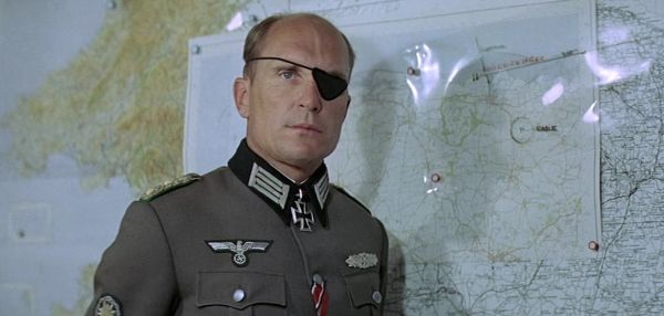 Robert Duvall in German uniform standing in front of a map