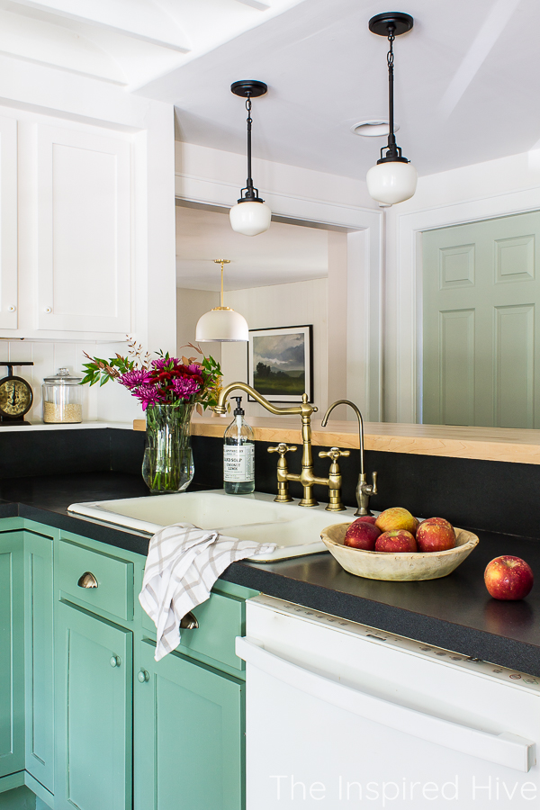 Green kitchen cabinets, black countertop, enamel sink, brass faucet, and schoolhouse lights.