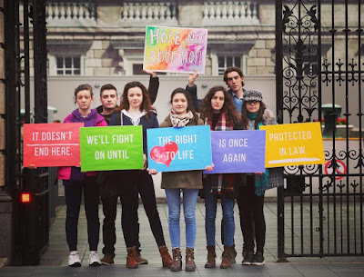 Irish young adults hold pro-life signs