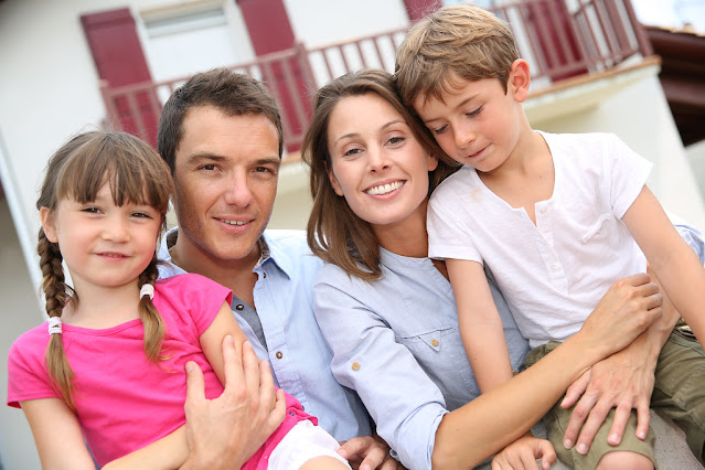 A stock image of a family of 4 in front of a house