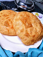Two puffy golden brown bhature along with chole