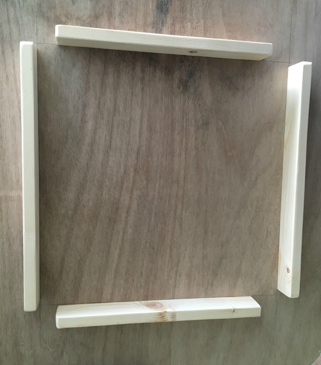 four-pieces-of-wood-attached-to-plywood-forming-a-square-frame