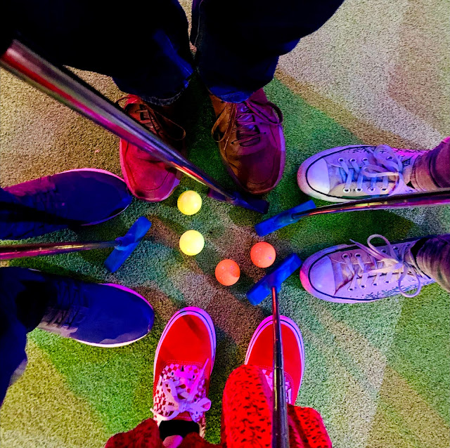 Four people's shoes surrounding golf balls and clubs
