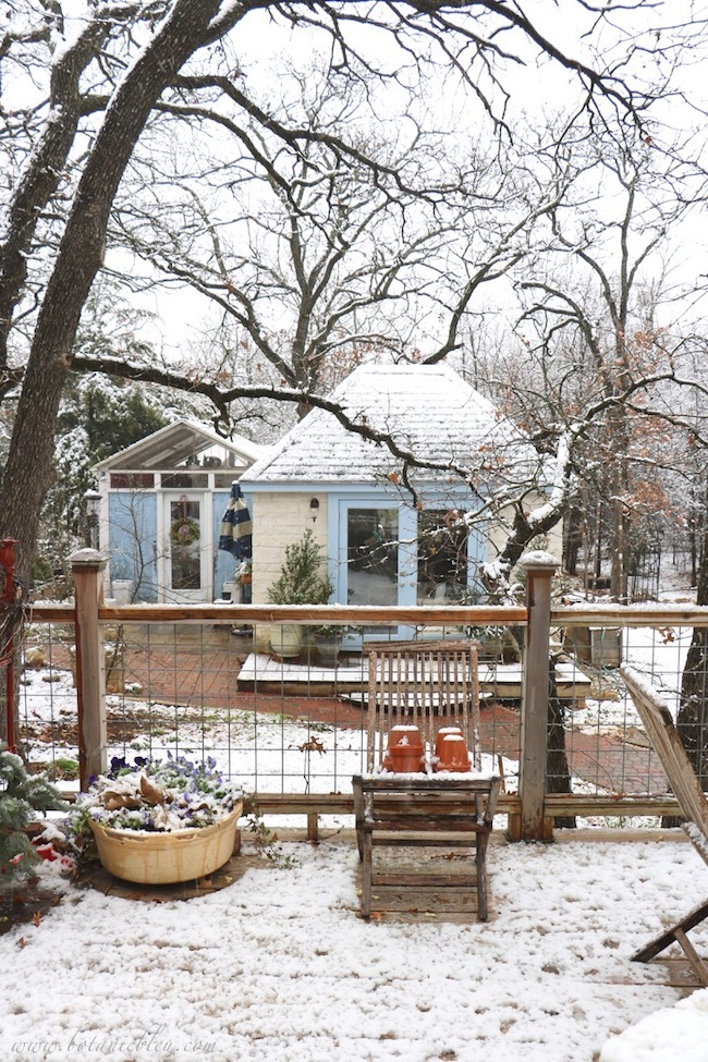 Deck railing made from galvanized wire does not block the view of the beautifulFrench Country garden shed in a snow covered woods