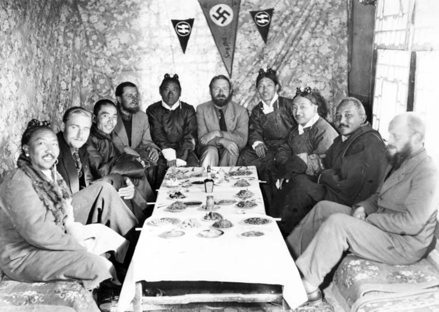 Under SS pennants and a swastika, the expedition members are entertaining some Tibetan dignitaries and the Chinese representative in Lhasa.