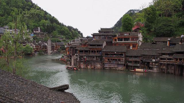 casas tradicionales de china a orillas del río Tuojiang con montañas alrededor