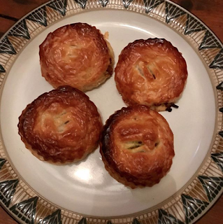 A plate with four nicely browned round puff pastry patties on.