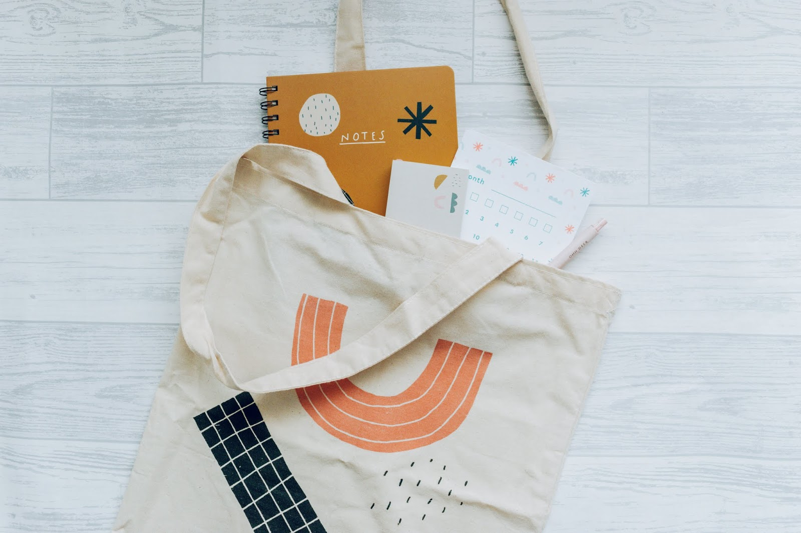 A nude tote bag with a geometric design and stationery showing out the top of the bag