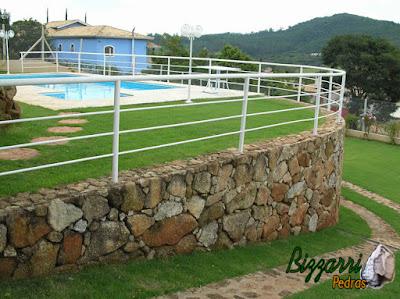 Construção da piscina em residência com os muros de pedra ornamental com os caminhos de pedra.