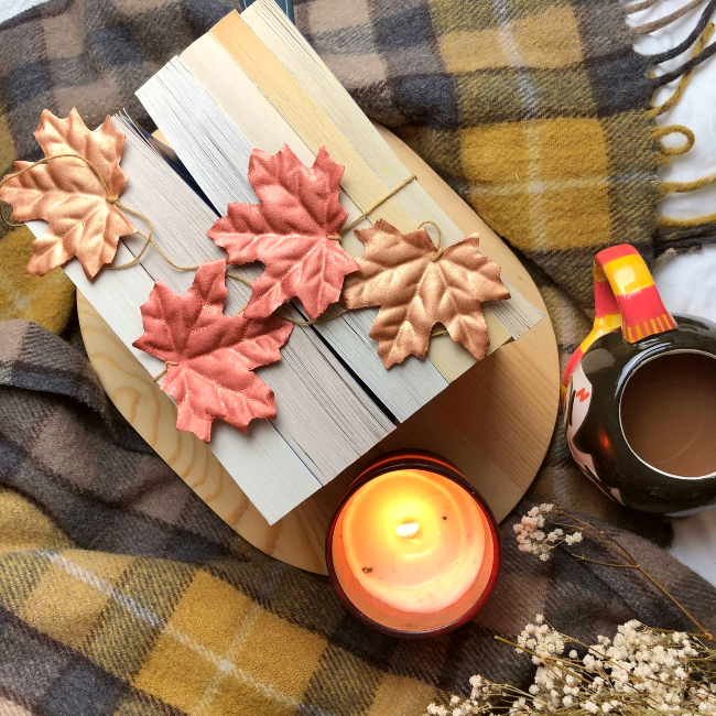 Books next to each with spines facing down and fake autumn leaves on top, next to a lit candle