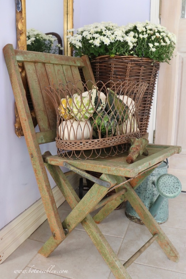 Small French Country rustic fall entry uses white mums, green gourds, chippy folding chair, and French flower basket to make a beautiful entry