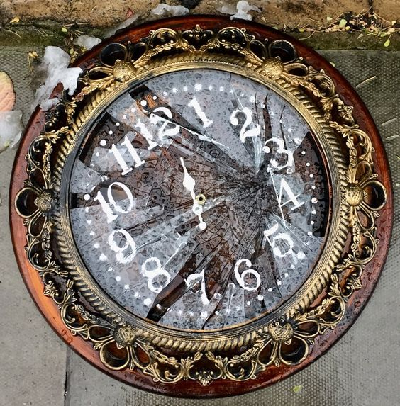 Broken ornate wall clock lying on the ground with shattered glass face