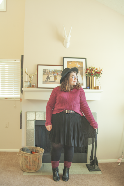 An outfit consisting of a black wide brim hat, a berry sweater half tucked into a black pleated mini skirt and black chelsea boots.