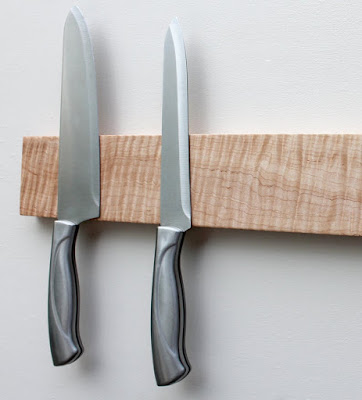 tiger maple wall-mounted knife rack with two knives hanging on it