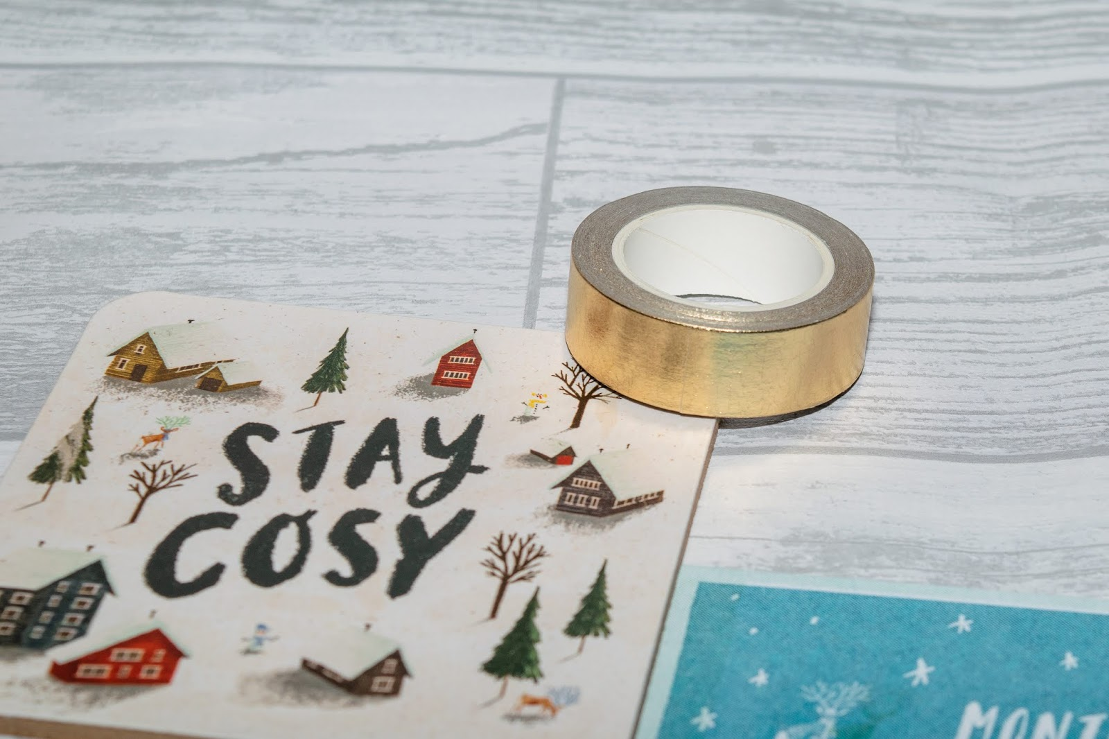 A gold foil washi tape on a cosy that says 'Stay Cosy' on the front.