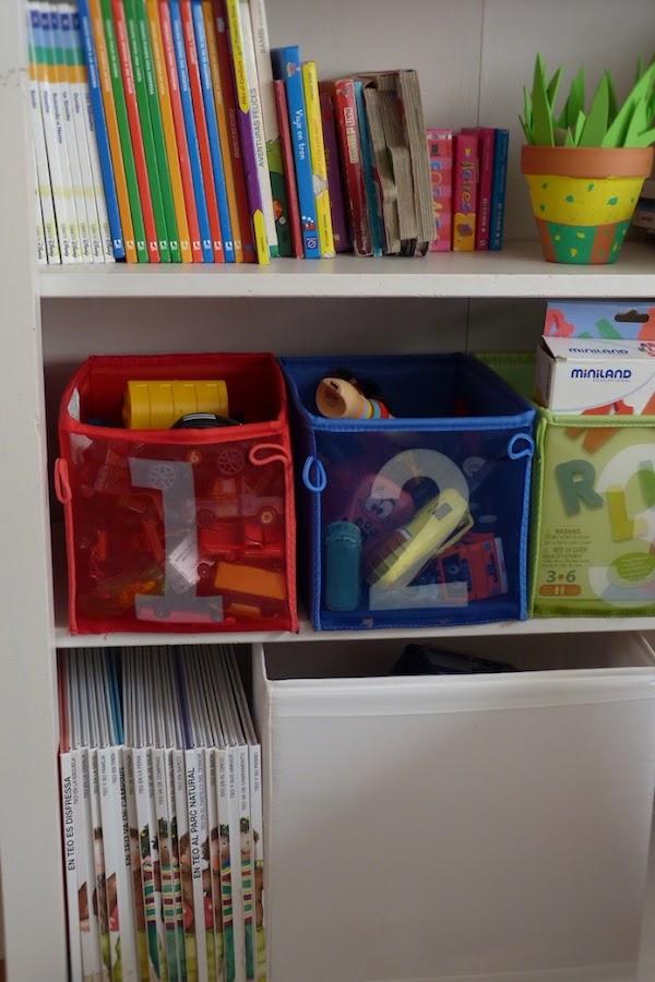 estantería con libros infantiles y cajas de juguetes