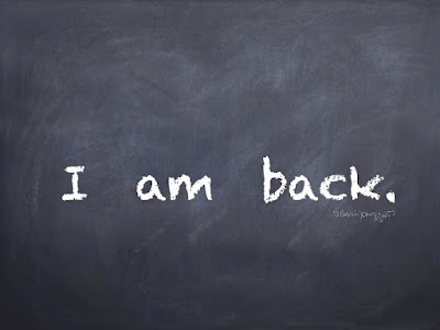 This is an image of a chalk board with the words I am back written on it.