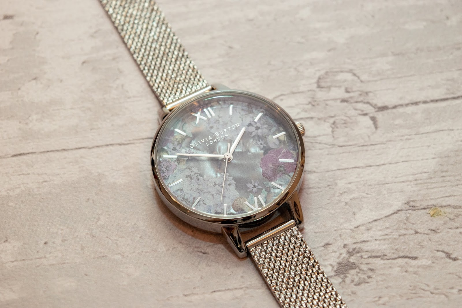 An Olivia Burton watch with a purple/lilac floral face and glittery silver strap.
