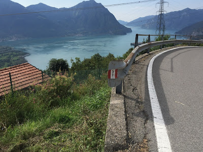 Signage for trail 551 on a guardrail with Lago d'Iseo below
