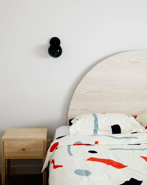 light wood half moon headboard, modern geometric duvet cover, modern black bulb sconce