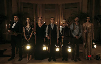 """Ready or Not"" (2019) movie still where Kristian Bruun, Melanie Scrofano, Andie MacDowell, Henry Czerny, Nicky Guadagni , Adam Brody, and Elyse Levesque stand next to each other with their old fashioned weapons drawn"
