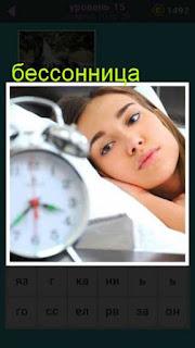 девушка в постели с будильником и открытыми глазами от бессонницы