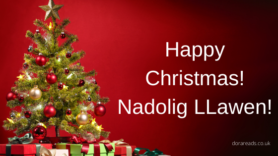 'Happy Christmas! Nadolig LLawen!' with red background, and Christmas tree with presents on the left-hand side