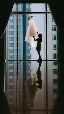 Novia mirando su vestido de novia en un contraluz en un ventanal