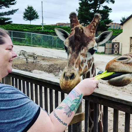 image of me smiling while I hand a romaine leaf to a giraffe, who reaches out his blue tongue to take it