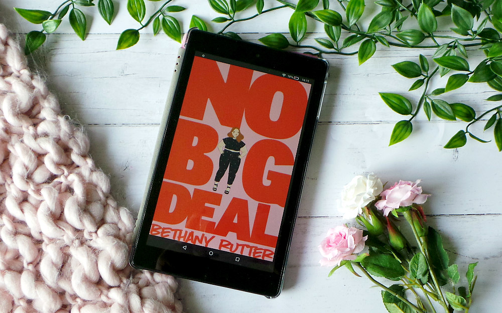 Kindle fire shows the cover of No big deal next to a pink chunky knit blanket, leaves and roses. The cover has no big deal written in big red letters on a pink background with a fat girl in place of the I.