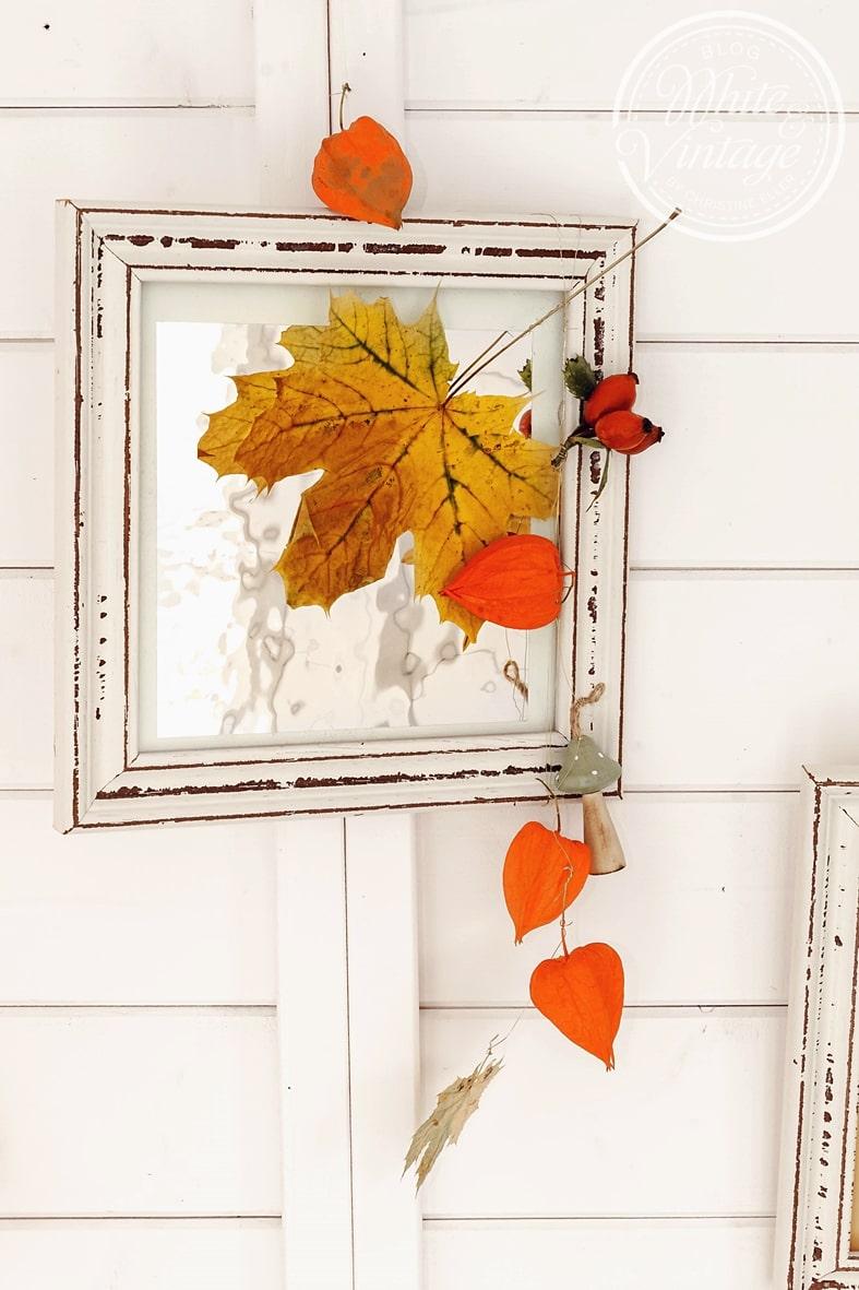 Farbenfrohe Herbstdeko aus Naturmaterialien und Bilderrahmen.