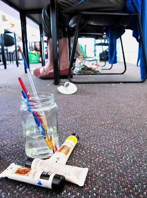 Jar with paint brushes, and paint tubes on a floor under a table at a workshop.
