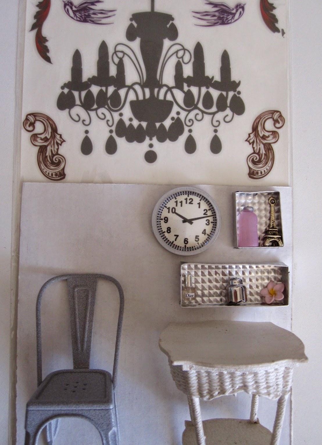 Selection of silver and white dolls house miniature furniture and accessories displayed under a rub-on chandelier sticker in its packet.