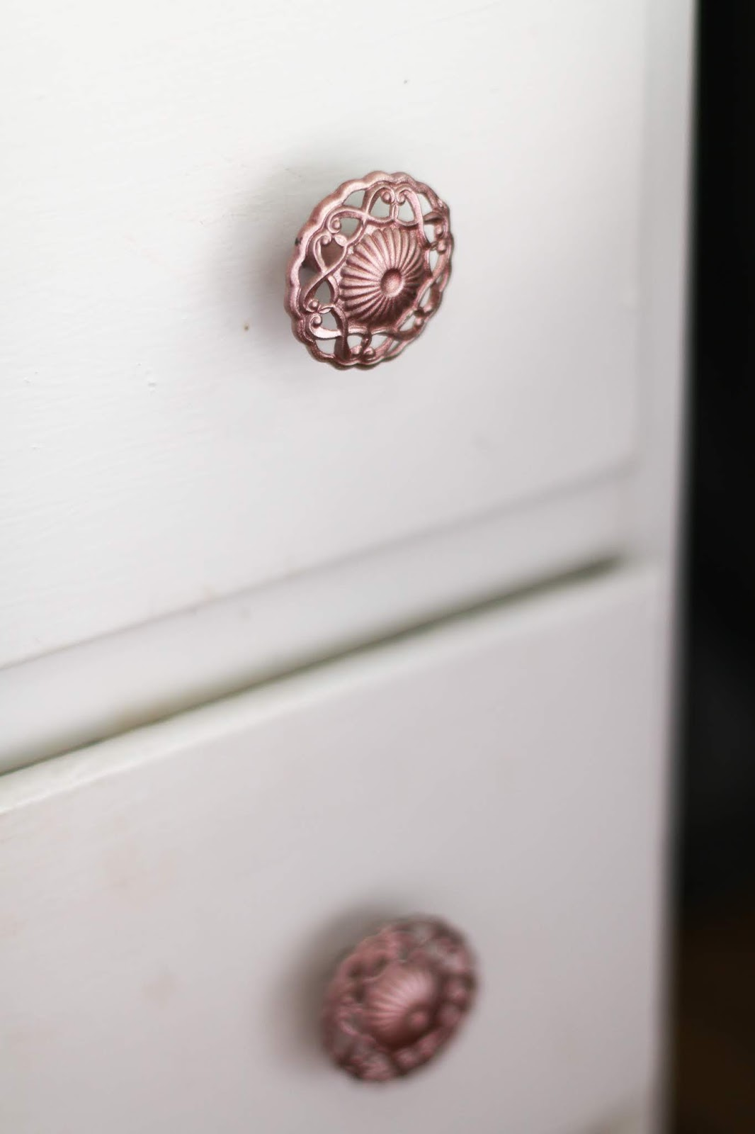 close up shot of the drawer handles after being spray painted rose gold on White drawers