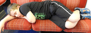boy asleep on train seats