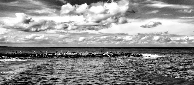 B&N.Pescadores sobre un espigón dentro del mar.