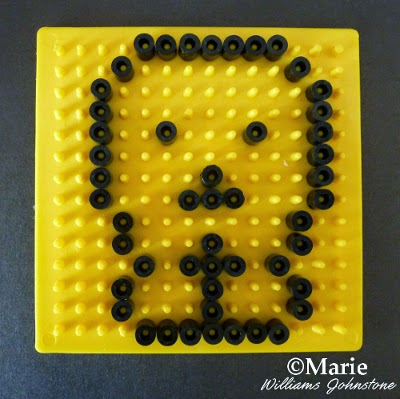 Yellow pegboard with beads outlining shape of a skull