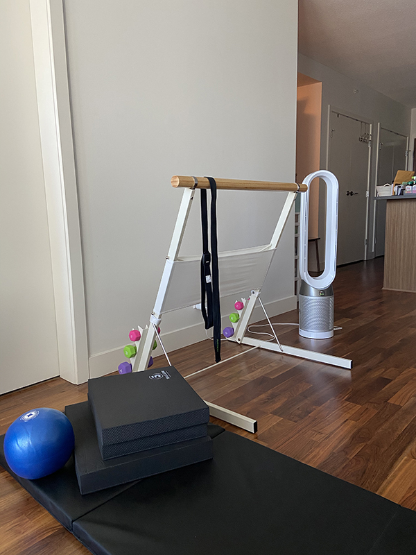 At-home barre workout setup featuring Bootykicker portable barre, Dyson fan, tri-fold exercise mat, foam physio mats, pilates ball, dumbbells, and yoga strap