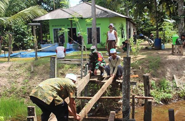 Pererat Tali Silahturahmi, Babinsa Tanjung Tengah Laksanakan Komsos Dan Gotong Royong Dengan Perbaiki Jembatan