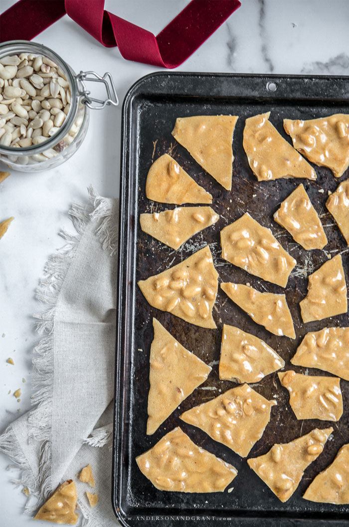 Baking sheet filled with pieces of peanut brittle.