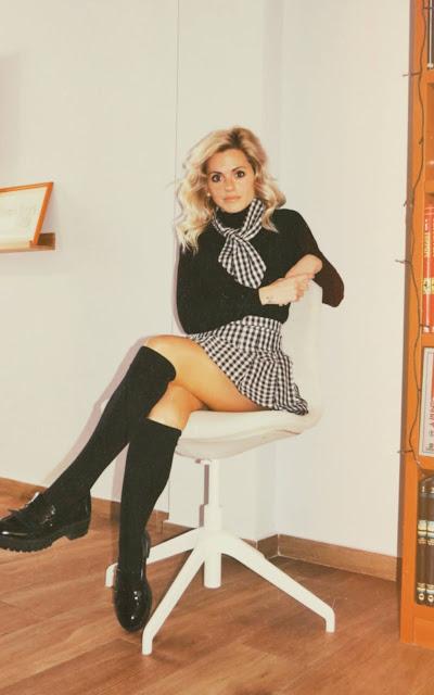 Alejandra Colomera vestida con jersey negro, falda de tablas cuadros vichy y lazo en el cuello vichy