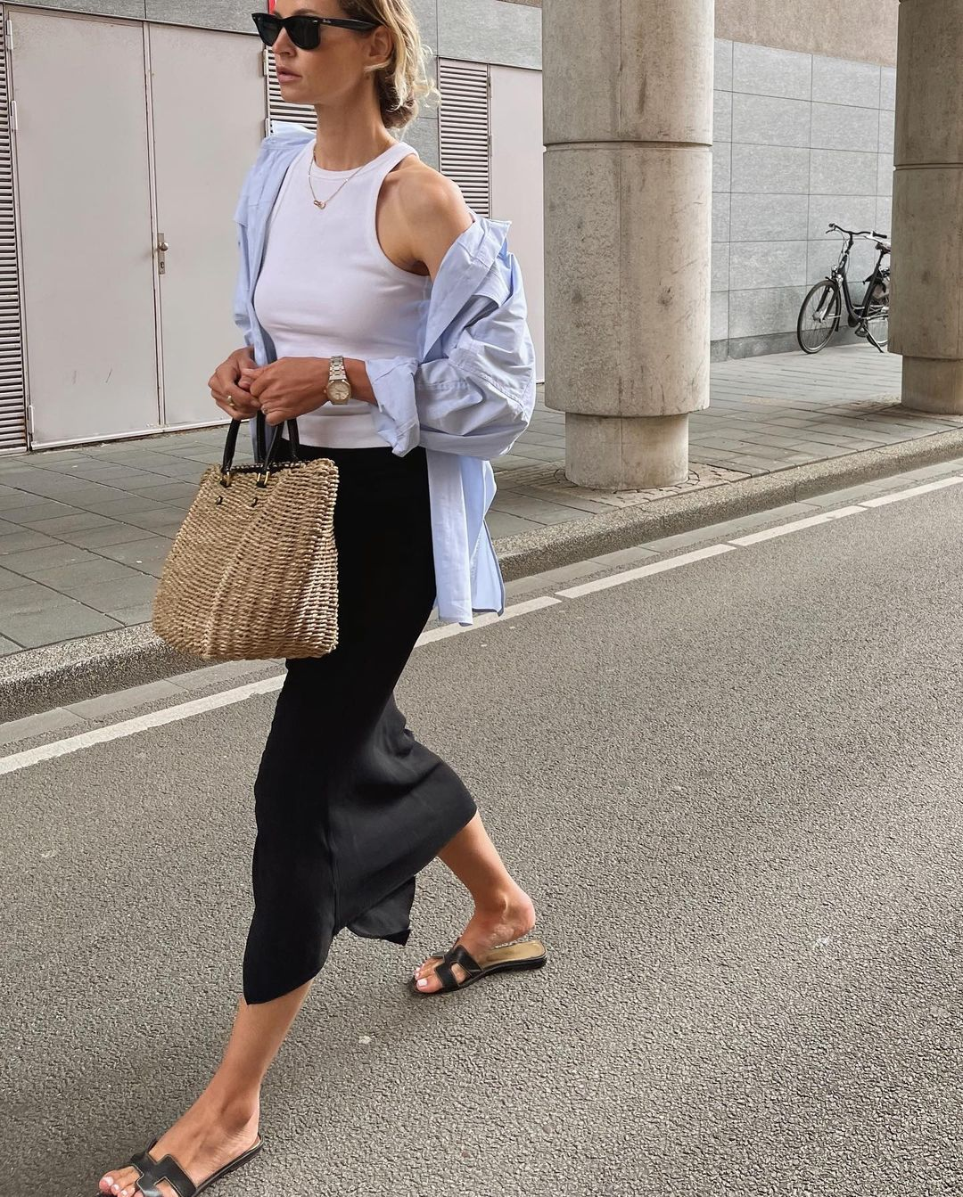 Easy Stylish Summer Outfit Inspiration — Anouk Yve in a blue button-down shirt, white racerback tank top, black midi slip skirt, Hermes flat slide sandals
