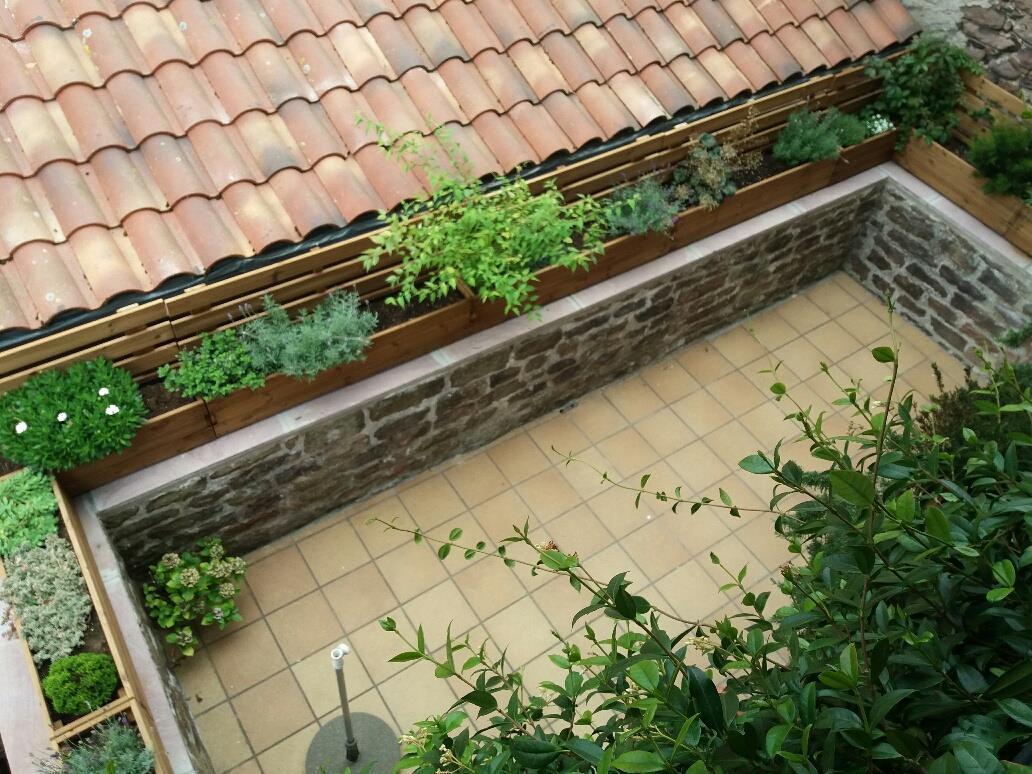 una terraza rustica bien bonita decorada con unas preciosas jardineras de madera con una celosa como complemento