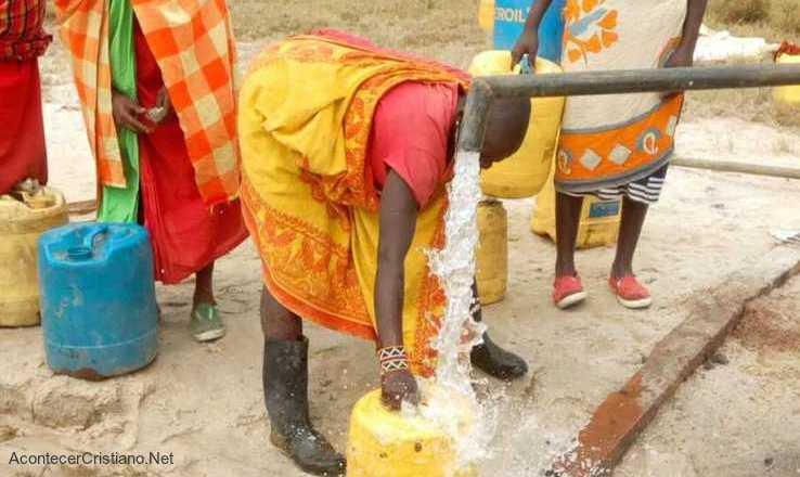 Mujer sacando agua de pozo en Kenia