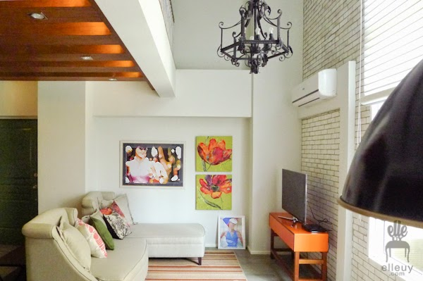 bright living room of a loft condo unit with white washed bricks and green and orange accent