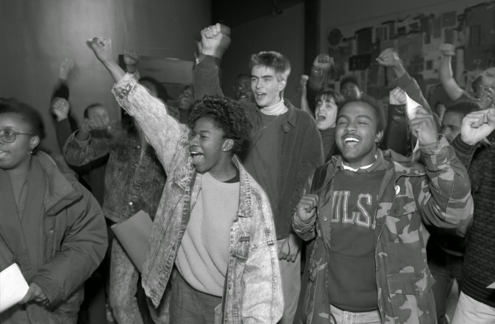 A black and white photograph of a group of smiling students with raised fists.