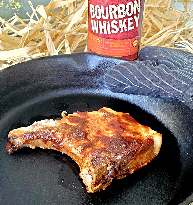 this is a cast iron skillet of pork chops with a bourbon barbecued glaze on top