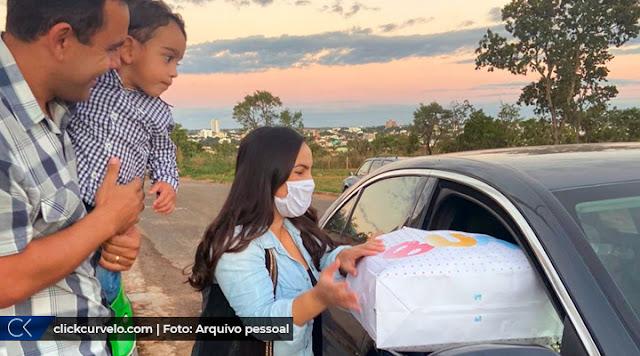 O pai Henrique Martins com o pequeno Henrique no colo ao lado da mãe, Karla Araújo, que recolhe um pacote de um carro. Todos sorrindo.