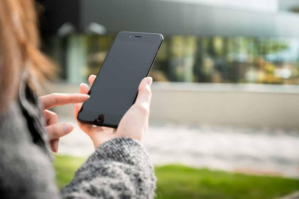 Mulher-segurando-um-celular-preto-nas-mãos