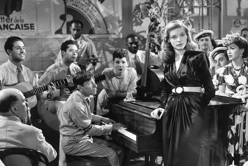 Lauren Bacall standing by a piano as musicians and others look on